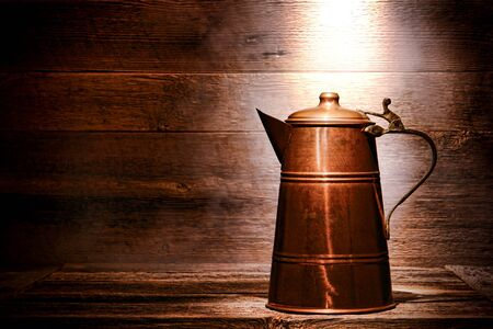 carafe: Old and antique vintage copper water pitcher or coffee pot with handcrafted brass handle on aged wood boards serving table in an ancient historic house  Stock Photo