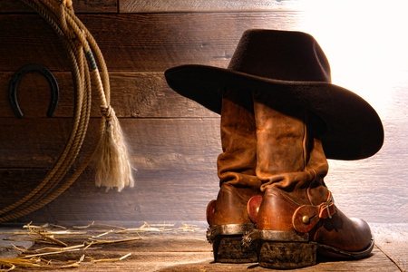 American West rodeo cowboy traditional black felt hat resting on worn leather working rancher roper boots with authentic Western riding spurs and lasso lariat in a vintage ranch wood barn photo