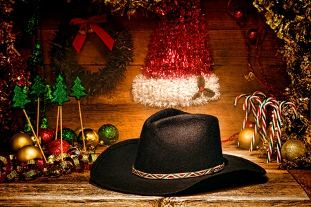 American West rodeo traditional black felt cowboy hat on wood vintage shelf with festive Christmas display decoration in an authentic country and western motif for a nostalgic Christmastime greeting card