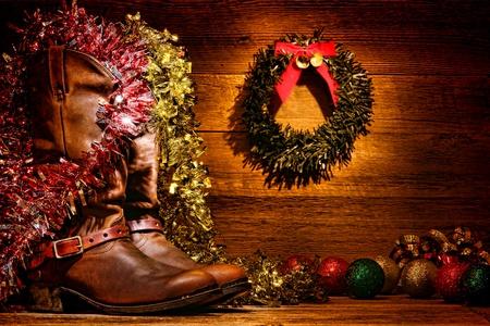 botas de navidad: Estilo occidental del rodeo botas de vaquero de cuero tradicionales en una cabaña de madera de la vendimia con la alegre decoración festiva pantalla de Navidad en un país auténtico y decoración occidental motivo para una tarjeta de felicitación de Navidad nostálgica