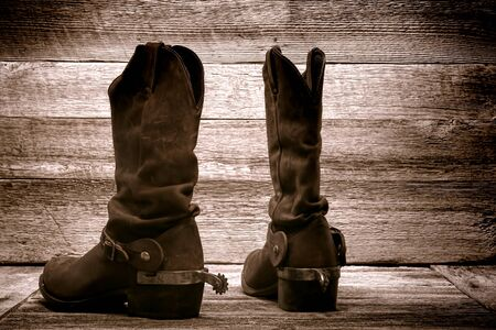 barn boots: American West rodeo cowboy pair of traditional leather roper style western riding boots with authentic ranching spurs in an old ranch wood barn Stock Photo
