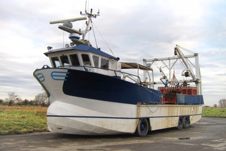 specialized: Specialized mussel fishing harvesting amphibious truck boat vehicle with wheels resting on dry land  Stock Photo