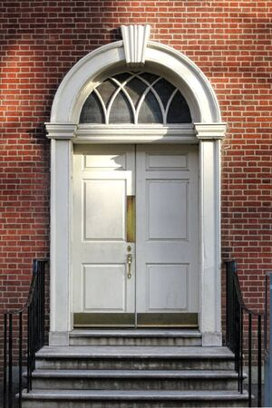 lintel: Georgian colonial architecture style old historic building entry door and steps with Adams detail semicircular fan lite above and keystone lintel at Independence Hall in Philadelphia Pennsylvania Stock Photo