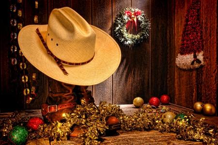 botas de navidad: American West rodeo tradicional de paja blanco sombrero de vaquero ranchero encima de las botas con decoración festiva pantalla de Navidad en un granero de madera auténtica país para un nostálgico tarjeta de felicitación de la Navidad occidental