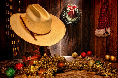christmas motif: American West rodeo traditional white straw cowboy hat atop rancher boots with festive Christmas display decoration in an authentic country wood barn for a nostalgic Western Christmastime greeting card