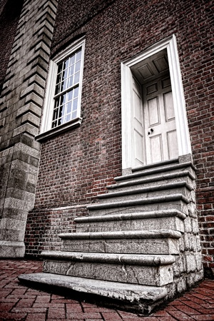Old historic brick building used granite steps stairway and wood panel entry door with window in antique wall photo