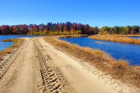 Rural sand covered unpaved and elevated dirt road crossing flooded marsh area and wetland bog in the countryside in the fall Stock Photo - 17420170