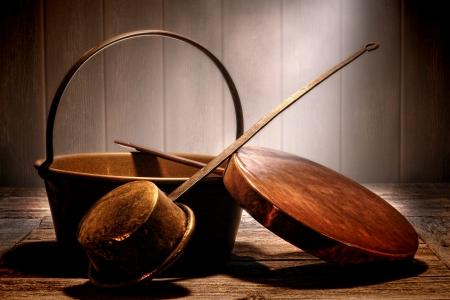 of copper: Cobre antiguo y ollas y sartenes de cobre amarillo del metal utensilio de cocina con asas de acero forjado en una desgastada mesa de preparaci�n de madera en una cocina antigua edad en una casa hist�rica