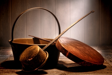 Old copper and brass metal pots and pans cooking utensil with forged steel handles on a weathered prep wood table in an aged antique kitchen in a historic home  Banque d'images