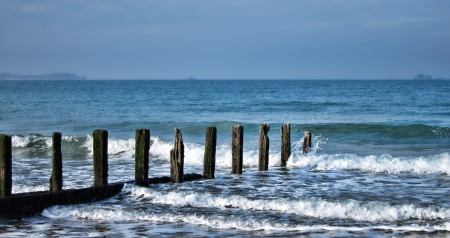 ebb: Old seaside wood post breakers partially submerged and breaking incoming sea waves on the English Channel coast in Brittany France Stock Photo