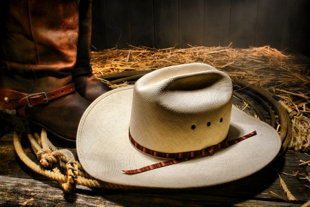 rodeo americano: American West rodeo tradicional de paja blanco sombrero de vaquero en un auténtico lazo occidental lazo con Roper botas de cuero en el suelo de madera en un granero rancho