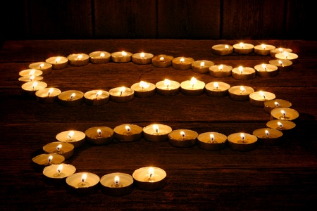 flame like: Lit meditation candles burning with soft glowing flame forming a Zen like curved path on old wood planks for prayer and reflection in a spiritual retreat temple  Stock Photo