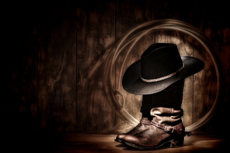 spurs: American West rodeo cowboy traditional black felt hat resting atop worn leather