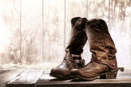 spurs: American West rodeo pair of traditional leather roper style western riding slouch cowboy boots with authentic ranching spurs on wood deck in front of an old ranch wood barn Stock Photo