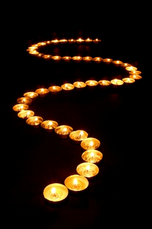 Lit meditation candles burning with soft glowing flame forming a Zen inspired curved path on black a surface for prayer and reflection in a spiritual retreat temple photo