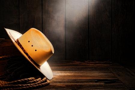 アメリカ西部ロデオ カウボーイ伝統的な白い麦わら帽子、煙やほこりの多い古い木製牧場の納屋で牧場のロープで木箱に柔らかい拡散光に照らされ