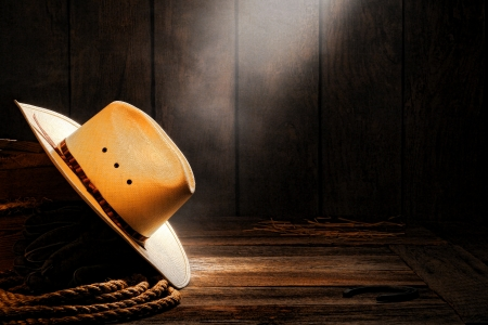 American West rodeo cowboy traditional white straw hat on a wooden box with ranching rope in a smoky and dusty old wood ranch barn lit by soft diffused light