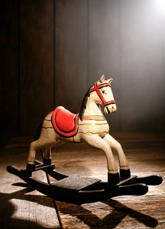 attic: Antique reproduction rocking horse wood toy on aged wooden plank floor in a dusty old house attic in a Nostalgic Americana scene