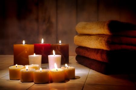 mimos: Cera velas ardiendo con llama suave que brilla intensamente y toallas de baño para un relajante spa y mimos sesión de tratamiento de la tarde en un spa de aromaterapia Foto de archivo