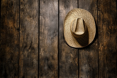 distressed: American West rodeo country farmer traditional straw hat hanging on distressed wood boards wall in a vintage ranch barn