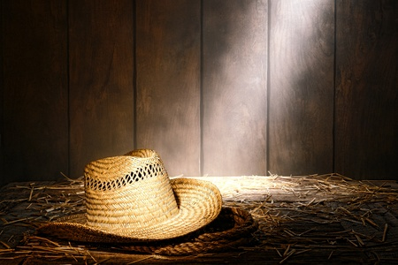 ranching: Old West farmer straw hat atop a sisal ranching rope on hay covered antique wood floor in a dusty vintage ranch hay barn lit by diffused sunlight