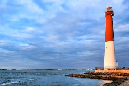 navigation aid: Barnegat lighthouse maritime navigation aid landmark tower in a scenic seashore seascape on the Atlantic coast of the New Jersey shore in sunset light