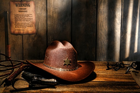 legends folklore: American West legend brown felt western cowboy hat on aged wood table sheriff desk with old lawman gun in holster and bullwhip in a dark county jail