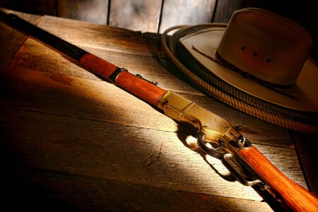 legend: American West legend antique western rifle shotgun with cowboy hat and lasso lariat on old wood table in a ranch barn