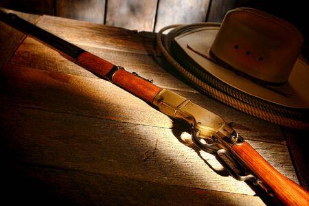 ranching: American West leyenda antigua occidental escopeta rifle con sombrero de vaquero y lazo lazo en la mesa de madera en un granero viejo rancho