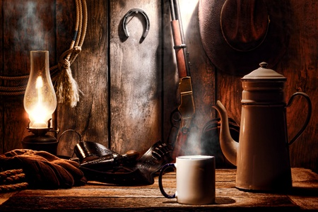 legend: American West legend cup of hot steamy coffee and brewing pot on an old wood table with traditional cowboy gear and aged tools in an antique western wooden cabin on a ranch