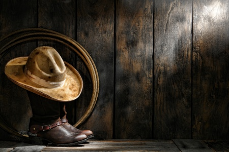 barn boots: American West rodeo cowboy dirty used felt hat atop worn leather working rancher roper boots with old spurs and lasso lariat in an antique ranch weathered wood cabin