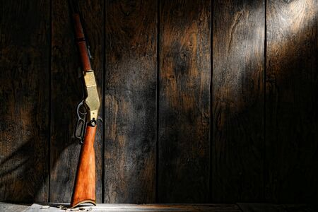 old rifle: American west legend repeating lever action rifle antique western gun and ammunition bullets on wooden floor in an old wood cabin on a vintage ranch  Stock Photo