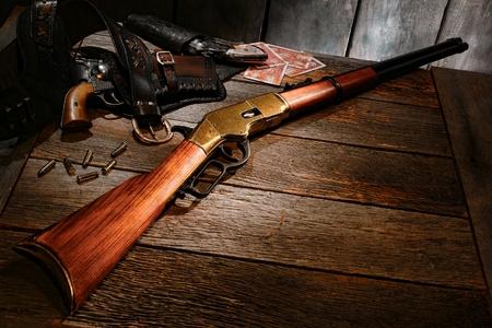 palanca: Oeste americano leyenda vendimia repetici�n rifle de palanca de acci�n y viejas armas antiguas occidentales en funda sobre una mesa de madera en una cabina de madera vieja en un rancho de la vendimia