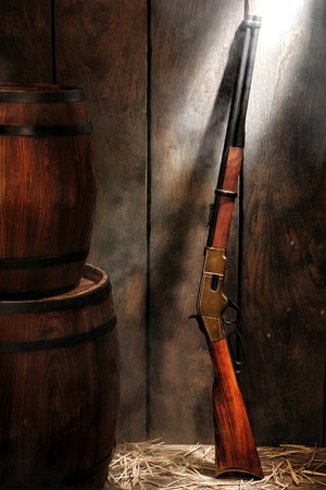 legend: American West legend repeating lever action rifle antique western gun and wood aged provision barrels in an old reserve stockroom with distressed wooden wall with light smoke Stock Photo