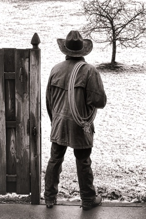 American West rodeo cowboy in western hat and leather jacket with lasso lariat on shoulder at ranch wood gate watching snow falling on prairie in cold winter weather