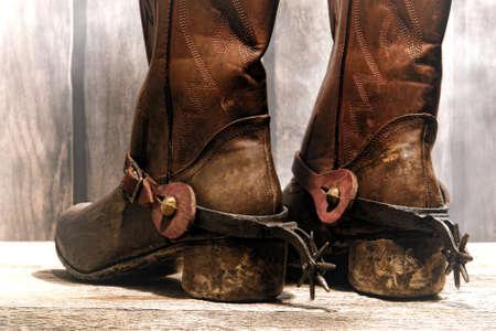 rodeo americano: American West rodeo vaquero botas de cuero tradicionales dificultades y desgastado talones traseros con antiguos estribaciones occidentales montar en un viejo rancho de madera del granero con neblina suave y difusa
