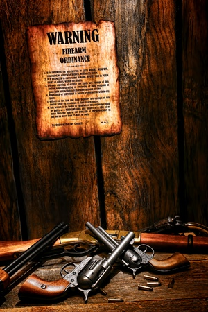 legend: American West legend old legal firearm ordinance poster with lawful weapon rules posted on sheriff office wood wall with pile of confiscated western guns and antique rifles