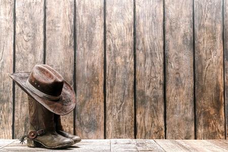 rodeo americano: sombrero de vaquero y sucias botas de cuero tradicionales de una cubierta de madera