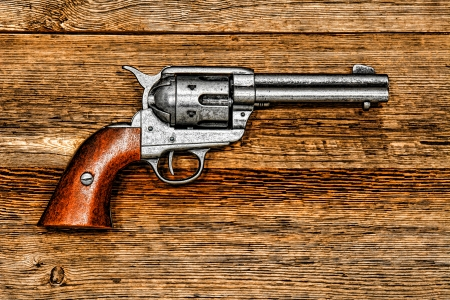 caliber: old style revolver antique six-shooter weapon gun on aged wood board  Stock Photo