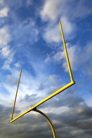 menacing: American football yellow goal posts over dramatic stormy blue sky with menacing gray clouds on the horizon