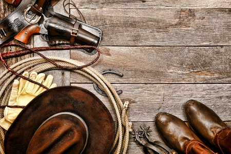 American West legend western cowboy traditional ranching gear still life with old revolver gun in leather holster along lariat lasso and antique hat near authentic boots and spurs on wood board ranch barn floor background