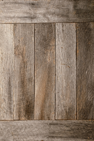 distressed wood: Old and distressed gray wood plank boards wall in an antique rural barn as an aged and weathered rustic background Stock Photo