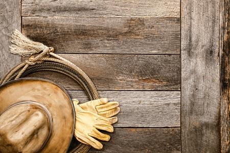 american rodeo: American West leyenda sombrero de vaquero tan vieja y sucia y un par de guantes de trabajo ranchero alto de una cuerda de lazo lazo en un viejo granero de madera tableros de piso en un granero rancho vendimia