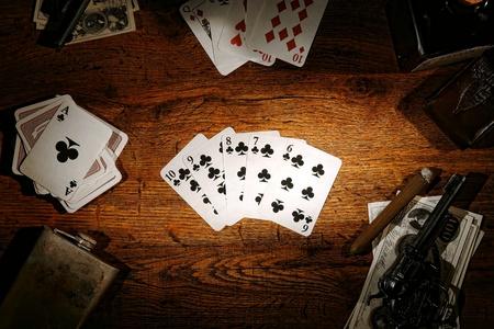 jeu de carte: American West légende vieux jeu de poker joueur à jouer aux cartes montrant une quinte flush sur une table en bois avec de l'argent et des armes à feu dans un salon de jeu