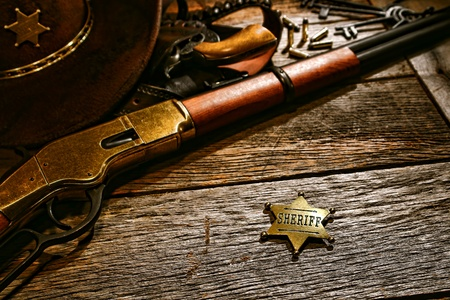 lawman: American West legend old sheriff lawman star shape justice symbol identification badge on weathered wood table office desk with shotgun rifle and western gun in holster under a hat in a historic county jail
