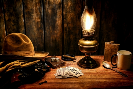 nightstand: American west legend cowboy worn hat atop gloves and gun in holster on an old Western hotel room wood nightstand table with vintage poker playing cards and traditional kerosene oil lamp lighting everyday life items in a nostalgic Americana scene
