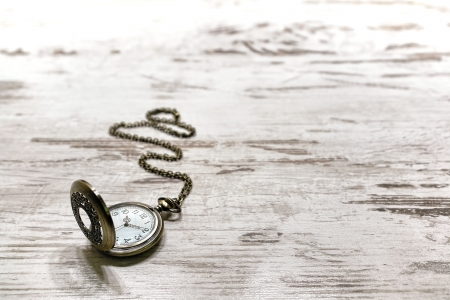 timekeeping: Vintage pocket watch and brass chain with scrolled detail and antique cardinal numbers keeping time on an old aged and weathered wood background  Stock Photo