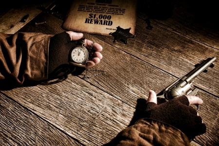 Amerikaanse Westen legende sheriff afgevaardigde die een antiek zakhorloge in zijn hand en het houden tijd over een voortvluchtige wilde beloning affiche terwijl een antieke westerse pistool en wachten op een vuurgevecht over een oude kantoor houten bureau Stockfoto