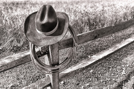 post: American West rodeo traditional cowboy hat and roping lasso lariat hanging on an old wood fence post near a western ranch field in black and white