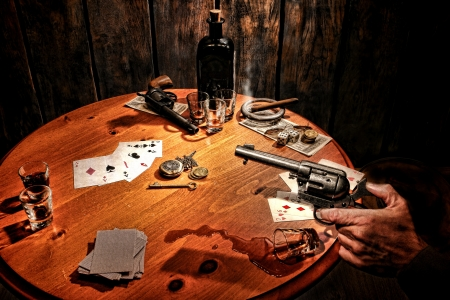 cheater: American West Legend armed gambler holding a revolver gun in his hand and threatening a cheater cowboy after a poker cards game incident with cheating and drinking in an old dark western gambling saloon scene